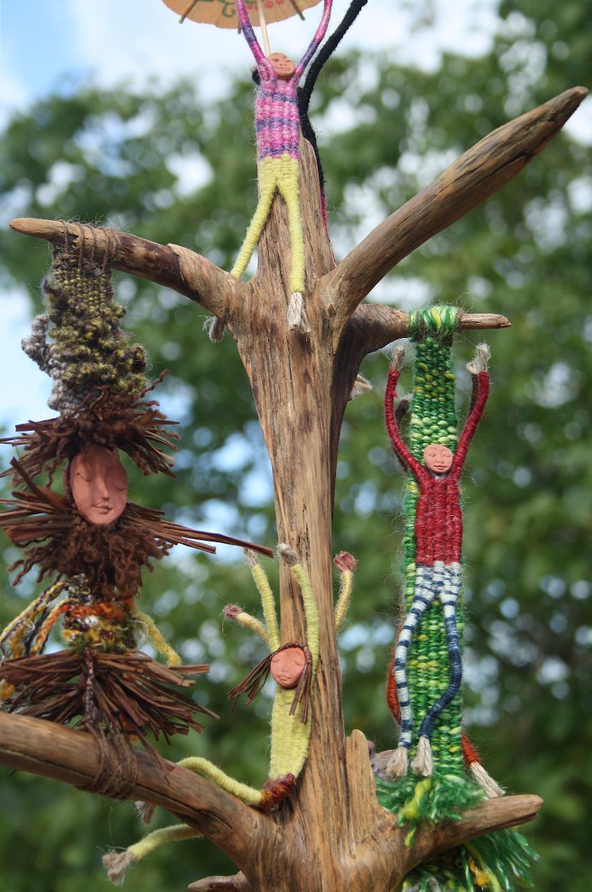 woven figures on tree